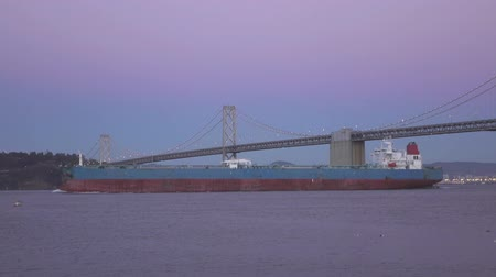 SLOW MOTION: Container ship leaving San Francisco port, shipping under the famous bridge