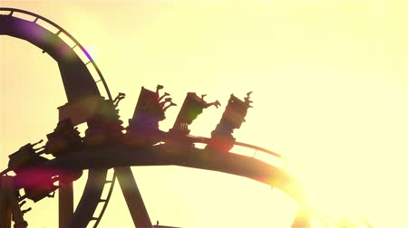 adrenalin : SLOW MOTION CLOSE UP: People riding upside down extreme rail roller coaster attraction in amusement park at golden sunset. Rail looping coaster ride over the setting sun. Dostupné videozáznamy