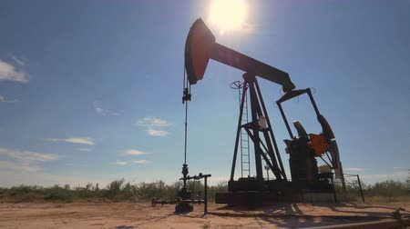 szamár : CLOSE UP: Industrial oil pump jack working and pumping crude oil for fossil fuel energy with drilling rig in oil field. Nodding donkey pump against the blue sky pumping over the sun in sunny summer Stock mozgókép