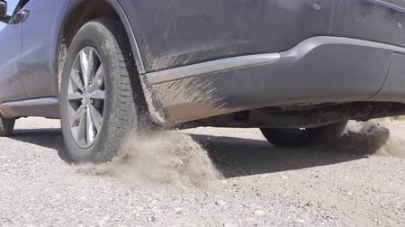 stop motion : SLOW MOTION CLOSE UP: SUV car starts and quickly drives away from a dusty parking lot raising a lot of dust while performing burn out in the middle of rocky desert in Texas