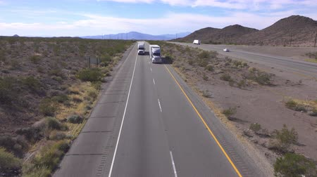 camionagem : AERIAL SLOW MOTION CLOSE UP: Cars and trucks driving on busy highway through the desert. Freight semi trucks transporting goods, personal cars on a road trip, people traveling in sunny summer