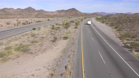 トラック輸送 : AERIAL SLOW MOTION CLOSE UP: Cars and trucks driving on busy highway through the desert. Freight semi trucks transporting goods, personal cars on a road trip, people traveling in sunny summer