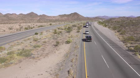 personal transporter : AERIAL SLOW MOTION CLOSE UP: Cars and trucks driving on busy highway through the desert. Freight semi trucks transporting goods, personal cars on a road trip, people traveling in sunny summer