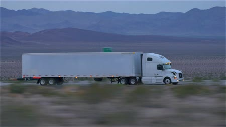 asfalto : CLOSE UP: Freight semi truck driving and transporting cargo container on empty highway, delivering goods