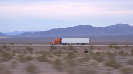 camionagem : CLOSE UP: Freight semi truck driving and transporting cargo container on empty highway, delivering goods