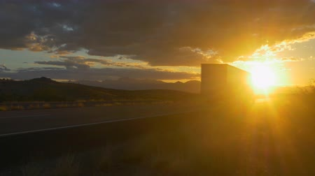 camionagem : CLOSE UP: Freight semi truck speeding on empty highway over golden sun at summer sunset. Transporting truck driving on freeway in sunny morning.