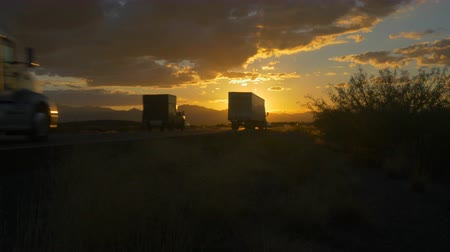personal transporter : CLOSE UP: Personal cars and big freight transporting semi trucks driving on busy highway at beautiful golden sunset in summer. Traffic on busy freeway speeding over the setting sun.