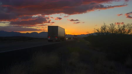 camionagem : CLOSE UP: Personal cars and big freight transporting semi trucks driving on busy highway at beautiful golden sunrise in summer. Traffic on busy freeway speeding in colorful early morning