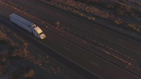 camionagem : AERIAL: Flying high above freight semi truck transporting goods on busy highway across the country in beautiful summer evening. Traffic driving and speeding on busy freeway at golden sunset