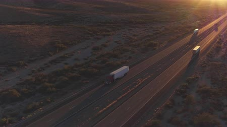camionagem : AERIAL: Flying high above cars and freight semi truck driving on busy highway across the country in beautiful summer evening. People on road trip traveling on busy freeway at golden sunset