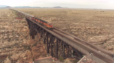 diablo : AERIAL: Two container freight trains crossing steel arch railroad bridge across the Canyon Diablo in the middle of the vast desert in Arizona. Rail freight transport delivering goods
