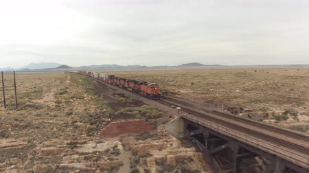 diablo : AERIAL: Container freight train crossing steel arch railroad bridge across the Canyon Diablo in the middle of the vast desert in Arizona. Rail freight transport delivering goods