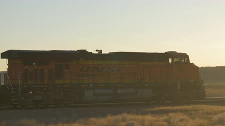 vagão : CLOSE UP: Locomotive moving long freight container train along the railroad tracks, transporting and delivering goods across the country at golden sunset