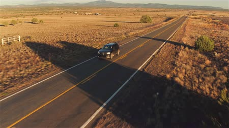 országúti : AERIAL: Young couple in black SUV car driving along empty countryside road at sunset. People traveling, road trip on historic Route 66 through beautiful meadow desert scenery in sunny summer