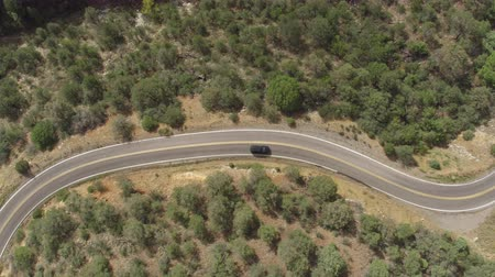 ziguezague : AERIAL: Black SUV jeep car driving along the winding mountain pass road through the forest. People traveling, road trip on curvy road through beautiful countryside scenery in sunny summer