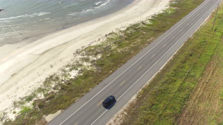 pilon : AERIAL: Black SUV car driving on countryside road along the Bay of Mexico. People traveling, road trip on empty road through beautiful countryside scenery in sunny summer