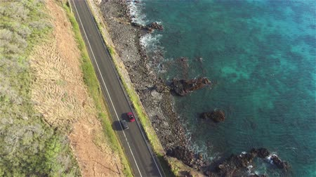 Оаху : AERIAL: Cars driving and overtaking on amazing picturesque coastal road above the ocean cliffs in beautiful Hawaii island