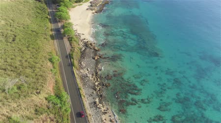 kabriolet : AERIAL: Red convertible car driving along beautiful coastal road in volcanic Hawaii island landscape with great ocean cliffs and pretty white sand beaches