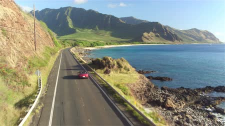 Оаху : AERIAL: Red convertible car driving along the picturesque coastal road above dramatic rocky shore towards beautiful volcanic mountains. Happy young couple on summer vacation traveling at the seaside