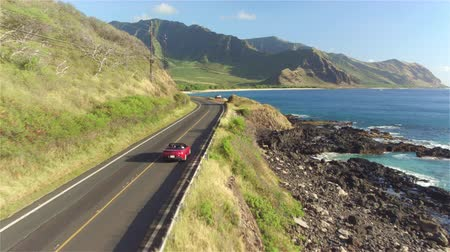 kabriolet : AERIAL: Red convertible car driving along the picturesque coastal road above dramatic rocky shore towards beautiful volcanic mountains. Happy young couple on summer vacation traveling at the seaside