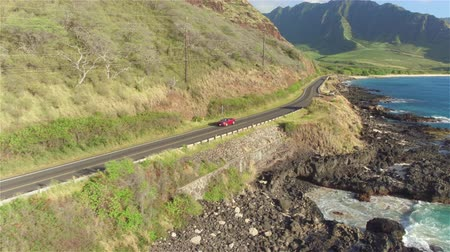 Оаху : AERIAL: Luxury red convertible car driving on picturesque coastal road along dramatic rocky shore on beautiful Hawaii. Happy young couple on summer vacation traveling at the seaside