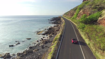 kabriolet : AERIAL: Luxury red convertible car driving on picturesque coastal road along dramatic rocky shore on beautiful Hawaii. Happy young couple on summer vacation traveling at the seaside