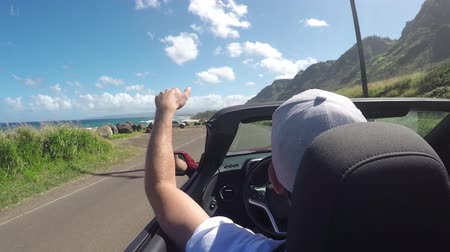 kabriolet : CLOSEUP: Happy man in open red convertible driving along coastal road in sunny Hawaii and playing with the wind. Smiling man on summer vacation traveling around the tropical island