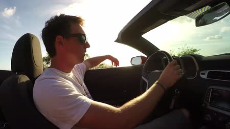 kabriolet : SLOW MOTION CLOSE UP: Happy young man in open convertible driving along coastal road at sunrise, playing with the wind. Smiling man on summer vacation traveling around the tropical island at sunset