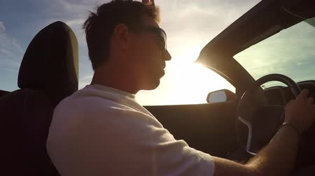 cabriolet : SLOW MOTION CLOSE UP: Happy young man in open convertible driving along coastal road listening music and celebrating. Cheerful man on summer vacation traveling around the tropical island at sunset Stock Footage