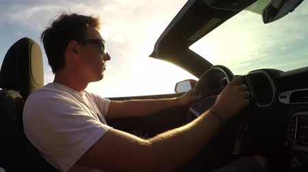 cabriolet : SLOW MOTION CLOSE UP: Cheerful young man driving in convertible, turning music volume up and nodding to the rhythm. Happy man on summer vacation traveling around tropical island at golden sunset Stock Footage
