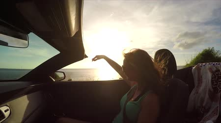 cabriolet : SLOW MOTION CLOSEUP: Happy young woman passenger riding in convertible with her hands raised, enjoying summer vacation. Cheerful woman with wind in her hair on driving around tropical island at sunset Stock Footage