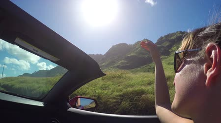 kabriolet : SLOW MOTION CLOSE UP: Smiling young woman in convertible car playing with wind and driving past the volcanic mountains in exotic Hawaii. Girl with wind in her hair traveling and exploring the island