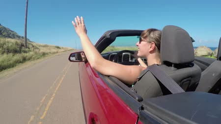 cabriolet : SLOW MOTION CLOSE UP: Happy young woman driving in convertible car along the coastal road, playing with wind in beautiful Hawaii. Smiling girl on summer vacation traveling and exploring the island Stock Footage