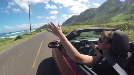 cabriolet : SLOW MOTION CLOSE UP: Smiling young woman driving in convertible car along the coastal road, playing with wind in beautiful Hawaii. Girl with wind in her hair traveling and exploring the island
