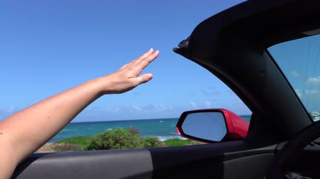 acenando : SLOW MOTION CLOSE UP: Driving in convertible car, hand playing with wind in summer. Unrecognizable female waving with her arm in the wind on exciting summer vacation in Hawaii island