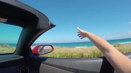 kabriolet : SLOW MOTION CLOSE UP: Driving in red convertible along the beach, arm outside of car playing with wind. Unrecognizable female waving with her hand in the wind on summer vacation in Hawaii island
