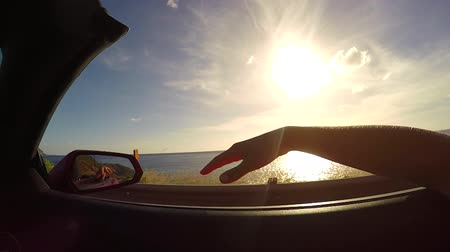kabriolet : SLOW MOTION CLOSE UP: Driving in red convertible, arm outside of car playing with wind against the sunset sky. Unrecognizable female waving with her hand in wind on summer vacation in Hawaii island