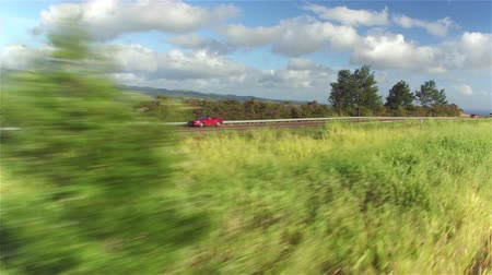 kabriolet : AERIAL CLOSE UP: Luxury red convertible car driving on countryside road along the stunning Waimea canyon in lush Hawaii island. Happy man and woman traveling on sunny summer vacation Wideo