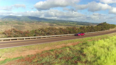 cabriolet : AERIAL CLOSE UP: Luxury red convertible car driving on countryside road along the stunning Waimea canyon in lush Hawaii island. Happy man and woman traveling on sunny summer vacation Stock Footage