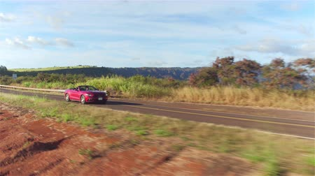 cabriolet : AERIAL CLOSE UP: Luxury red convertible sports car driving on countryside road along stunning majestic Waimea canyon in lush Hawaii island Kauai. Happy man and woman traveling on sunny summer vacation Stock Footage
