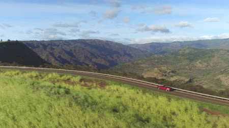kabriolet : AERIAL CLOSE UP: Luxury red convertible sports car driving on countryside road along stunning majestic Waimea canyon in lush Hawaii island Kauai. Happy man and woman traveling on sunny summer vacation Wideo