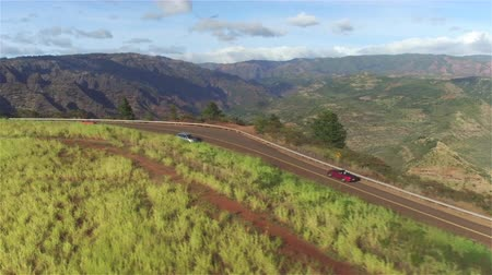 formasyonlar : AERIAL CLOSE UP: Luxury red convertible sports car driving on countryside road along stunning majestic Waimea canyon in lush Hawaii island Kauai. Happy man and woman traveling on sunny summer vacation Stok Video