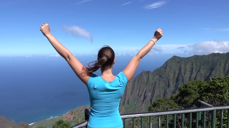 kabarık : SLOW MOTION CLOSE UP: Cheerful young woman tourist on a mountain lookout point admiring stunning view in Hawaii, victoriously outstretching arms up in the air. Happy girl raising hands proudly