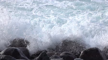 waterdrop : SLOW MOTION CLOSE UP: White ocean wave hitting hard on black volcanic rocks on wild beach forming white foam and massive splashes of water. Foams spraying and splashing over dark stones Stock Footage