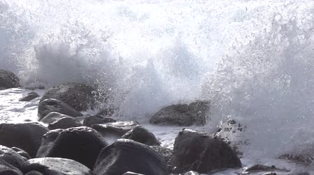 kayaçlar : SLOW MOTION CLOSE UP: Huge ocean wave hits hard on round black volcanic rocks and stones on wild beach forming white foam and massive splashes of water. Foams spraying and splashing over dark stones Stok Video