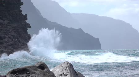 театральный : SLOW MOTION: Dramatic powerful ocean wave uprising from the restless emerald sea, splashing and crushing into majestic crag ocean cliff. Unstoppable ocean weaves spewing salty spray against rocky wall