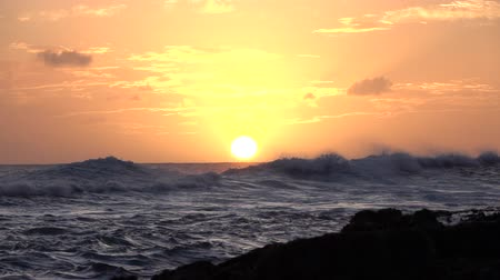 slapping : SLOW MOTION: Beautiful wild curly wave splashing on the sea surface on stunning summer evening with golden sun in the background. Pretty blue ocean curls splattering   on amazing golden summer sunset