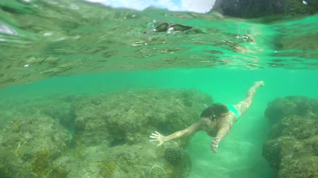 kumlu : SLOW MOTION HALF UNDERWATER: Young girl swimming in crystal clear emerald shallow waters above amazing rocky coral reef with dense lush exotic rainforest and green mountain range in the background
