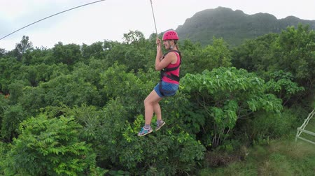 hamlet : Young happy woman sliding on high speed zipline rope above beautiful tropic deciduous forest. Adrenaline gravity traveling from the top of the hill with overgrown jungle mountain in the background