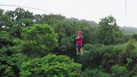 zipline : Young happy woman traveling high speed zipline rope above beautiful tropic deciduous forest. Girl having fun riding cable zipline above stunning impassable overgrown lush tropical rainforest